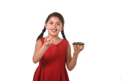 Latin female child in red dress eating chocolate donut with hands and mouth stained and dirty smiling happy Royalty Free Stock Photos