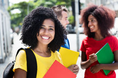 Latin female student with curly black hair and friends. Outdoor in the city Stock Photos