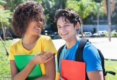 Latin female student talking with caucasian boyfriend Stock Photos