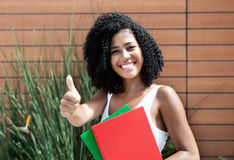 Latin female student woman with curly black hair showing thumb. Outdoor Stock Images