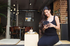 Latin female using touch pad during coffee break in restaurant outdoors Stock Images