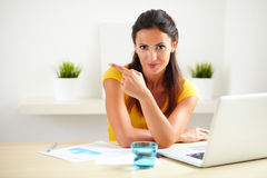 Latin female worker sitting in her office. Latin female worker in a company sitting in her office while pointing to her right and looking at you - copyspace Stock Photos