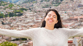 Latin freedom girl take the rays of sun over her face while she smiled happily when a colonial city is located behind. Her Stock Images