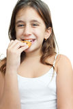 Latin girl eating a chocolate chips cookie. Beautiful latin girl eating a chocolate chips cookie isolated on white Royalty Free Stock Images