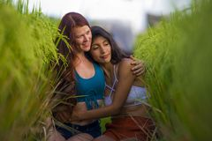 Latin girl and her attractive Caucasian girlfriend both women enjoying Summer holidays having fun together on rice field smiling. Young beautiful latin girl and stock images