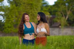 Latin girl and her attractive Caucasian girlfriend both women enjoying Summer holidays having fun together on rice field smiling. Young beautiful latin girl and royalty free stock photo