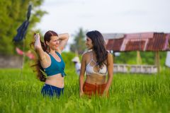 Latin girl and her attractive Caucasian girlfriend both women enjoying Summer holidays having fun together on rice field smiling. Young beautiful latin girl and royalty free stock image