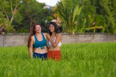 Latin girl and her attractive Caucasian girlfriend both women enjoying Summer holidays having fun together on rice field smiling. Young beautiful latin girl and royalty free stock photography