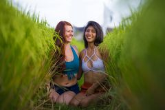 Latin girl and her attractive Caucasian girlfriend both women enjoying Summer holidays having fun together on rice field smiling. Young beautiful latin girl and stock photography