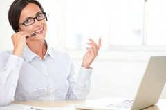 Latin girl receptionist conversing on her earphone Stock Images