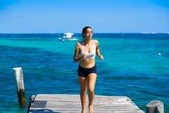 Latin girl running in caribbean pier beach of Mayan Riviera Stock Photography