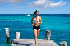 Latin girl running in caribbean pier beach of Mayan Riviera Stock Photo