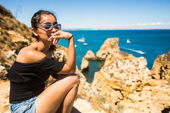 Latin Girl sitting on a cliff and enjoy the summer time near Atlantic ocean in Portugal Royalty Free Stock Image
