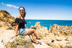 Latin Girl sitting on a cliff and enjoy the summer time near Atlantic ocean in Portugal Stock Photos