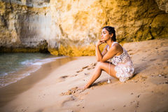 Thinking latin girl sitting on sand at beach and looking at ocean feel alone. Summer vocation Stock Photo