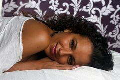 Latin girl smiling on bedsheets Royalty Free Stock Image