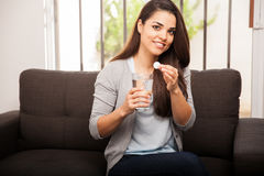 Latin girl taking an antacid. Cute young Latin girl taking an antacid for her stomach ache and smiling Royalty Free Stock Photo