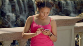 Latin girl using smartphone at park. African woman using phone outdoor. Digital lifestyle concept. Smart watch on hand. Girl phone. Young woman look phone stock footage