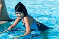 Latin girl water exercising. Happy smiling beautiful latin girl exercising with water aqua bike in a swimming pool Stock Image