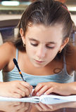 Latin girl working on her homework Stock Photo