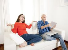 Latin girlfriend unhappy , angry and frutrated with boyfriend playing on laptop Royalty Free Stock Photography