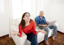 Latin girlfriend unhappy , angry and frutrated with boyfriend playing on laptop Stock Photos