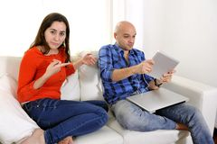 Latin girlfriend unhappy , angry and frutrated with boyfriend playing on laptop Royalty Free Stock Images
