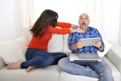 Latin girlfriend unhappy , angry and frutrated with boyfriend playing on laptop. Latin couple sitting on couch with girlfriend angry and boyfriend always working royalty free stock photos