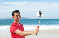 Latin guy at beach talking a picture with his phone and selfie stick Royalty Free Stock Photo