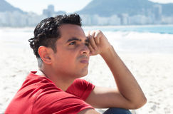 Latin guy at beach thinking about problems Royalty Free Stock Photography