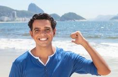 Latin guy at Copacabana beach pointing at Sugarloaf mountain Royalty Free Stock Photography