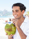 Latin guy enjoying coconut water at beach Stock Photography