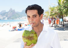 Latin guy likes coconut water at beach Royalty Free Stock Images