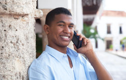 Latin guy with phone in a colonial town laughing at camera. With palms and buildings in the background Stock Image