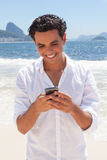 Latin guy typing message at Copacabana beach Stock Photo