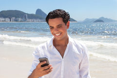 Latin guy writing message at Copacabana beach Stock Image