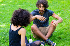 Latin Hipster couple sitting on meadow Stock Images