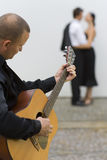 Latin Love. A street musician playing his guitar serenades two young lovers Stock Photos