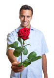 Latin lover with a red rose. Handsome latin man with a red rose for his girlfriend on a white background Royalty Free Stock Images