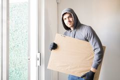 Male robber stealing a piece of art. Latin male criminal leaving a house with a stolen piece of art and making eye contact Stock Photography
