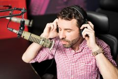 Latin male radio host in studio. Handsome young latin male radio host adjusting his headphones while sitting in front of a microphone in studio Stock Image