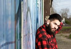 Latin man with beard and piercings sitting outdoors Royalty Free Stock Images