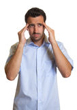Latin man in a blue shirt has a headache Stock Images