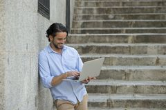 Latin man on city staircase working with laptop computer looking satisfied and confident. Young attractive latin man on city staircase working with laptop Stock Image