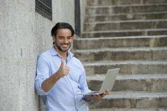 Latin man on city staircase working with laptop computer looking satisfied and confident. Young attractive latin man on city staircase working with laptop Royalty Free Stock Photos