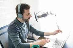 Latin man hosting online radio. Profile view of handsome young latin man using laptop and taking into microphone, hosting online radio Royalty Free Stock Photo