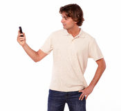 Latin man in jeans reading on cellphone Royalty Free Stock Photos