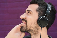 Latin man listening music with headphones. Portrait of young latin man listening to music with headphones. Outdoors Royalty Free Stock Images