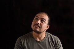 Latin man looking up on black. Background Royalty Free Stock Photos