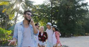 Latin Man Making Call Using Cell Smart Phone People Group Talking In Tropical Palm Tree Park. Slow Motion 60 stock video footage